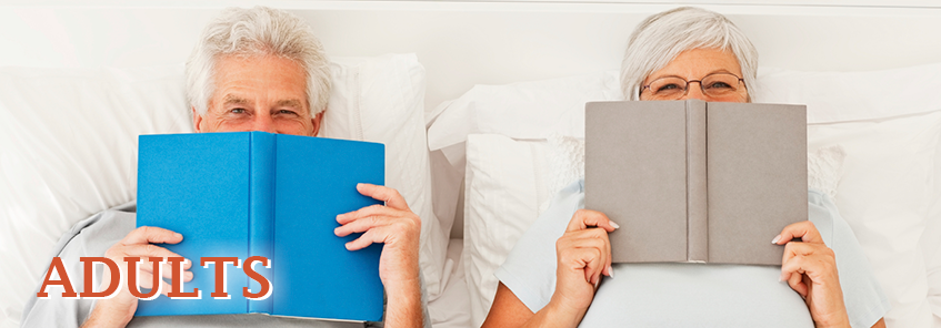 Two older adults reading books in bed